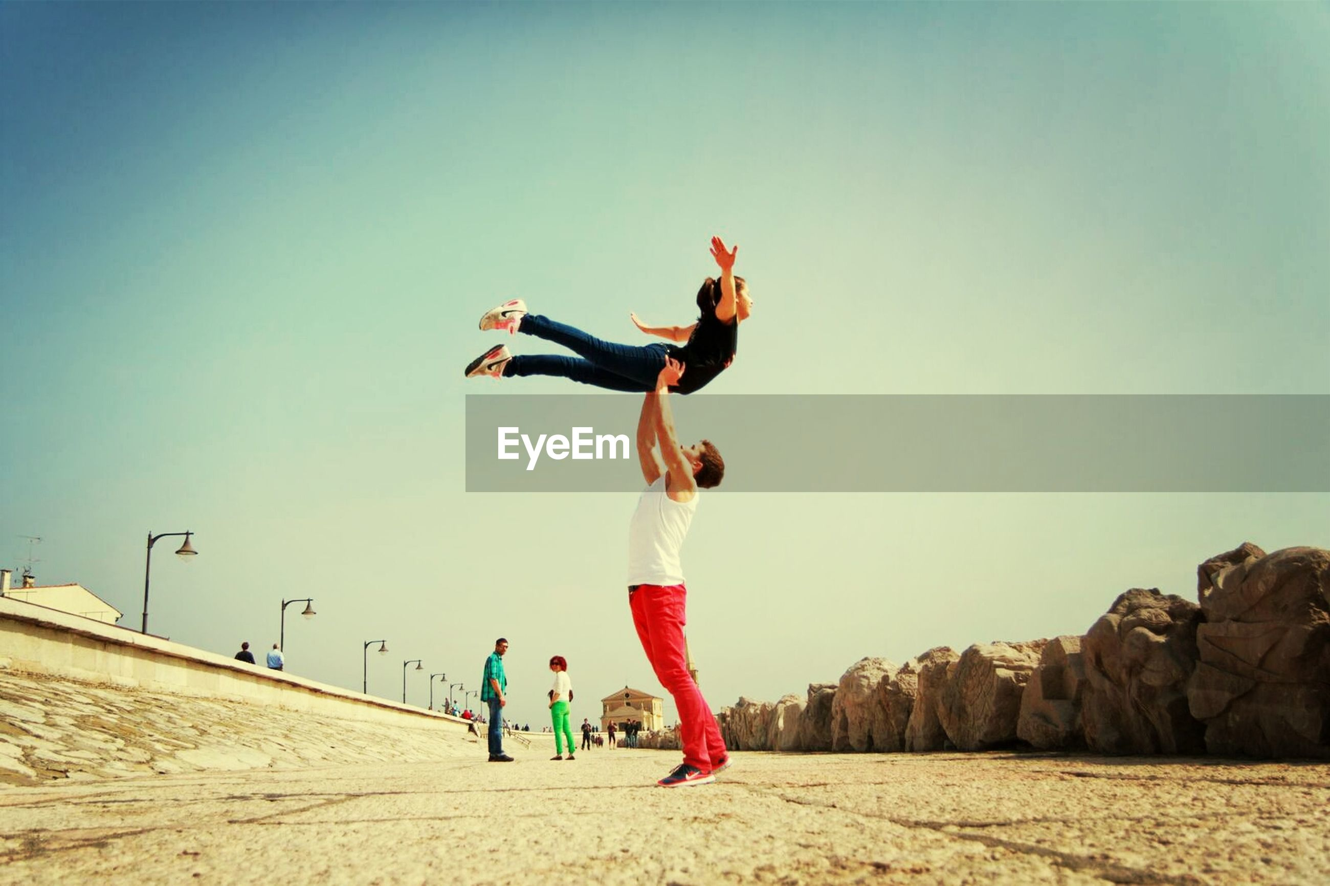 full length, lifestyles, leisure activity, casual clothing, togetherness, childhood, fun, enjoyment, boys, clear sky, vacations, arms outstretched, sky, mid-air, girls, copy space, sand