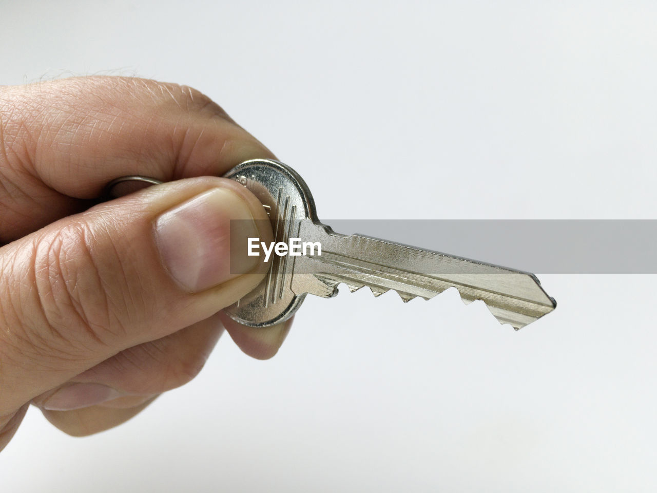 Cropped hand of man holding key against white background