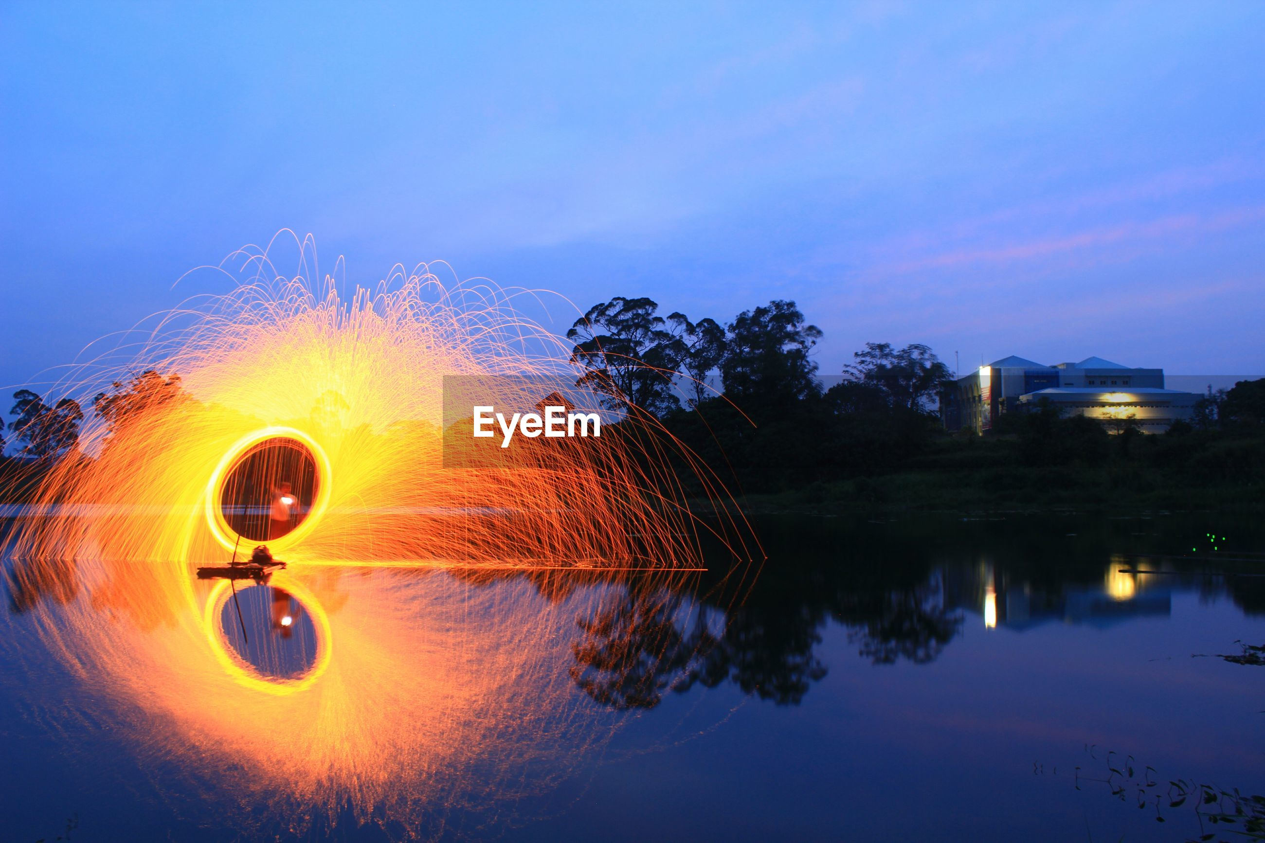 Reflection of illuminated trees on water at sunset