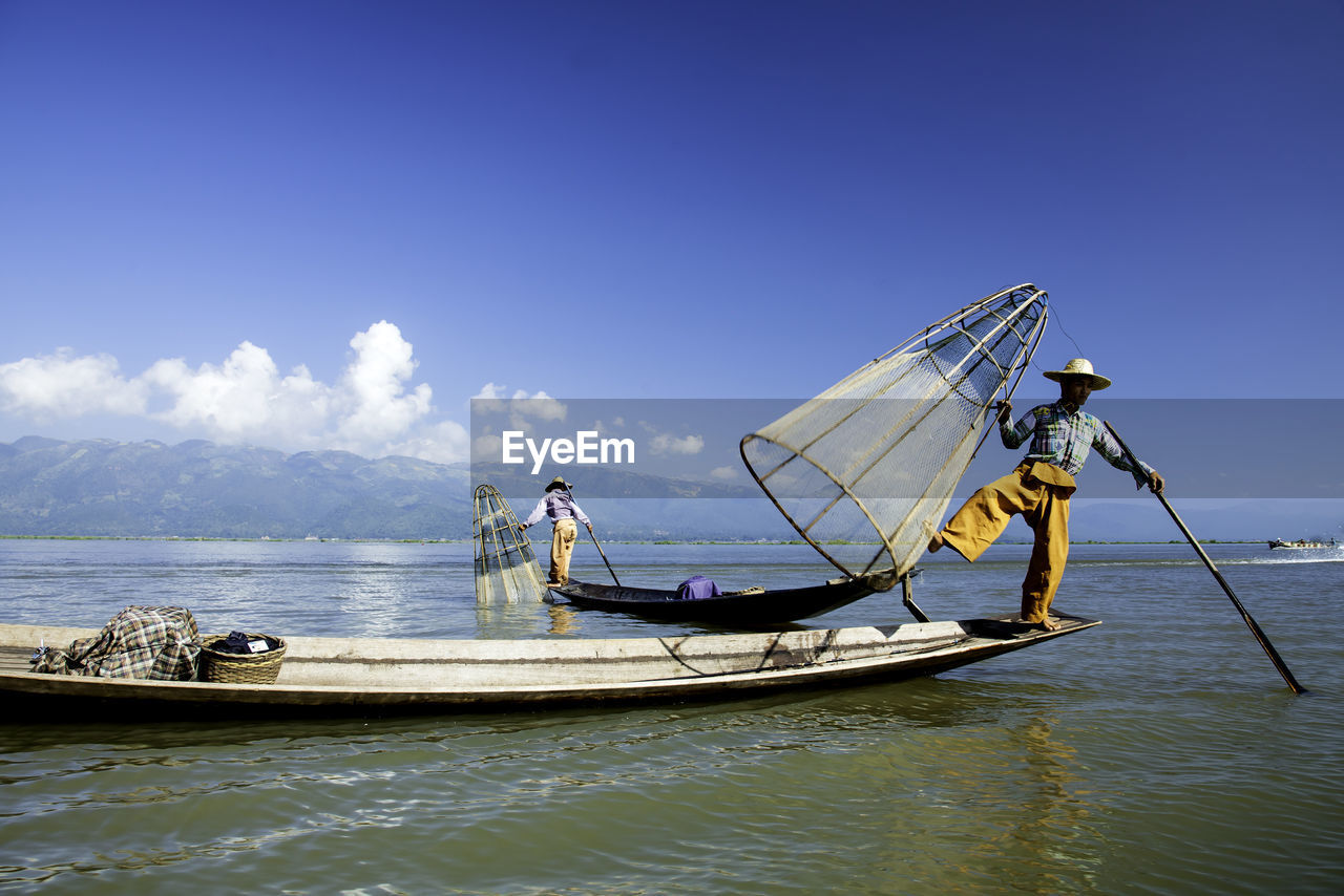 nautical vessel, mode of transportation, sky, transportation, water, real people, sea, day, waterfront, men, occupation, nature, beauty in nature, fisherman, one person, outdoors, standing, scenics - nature, fishing industry