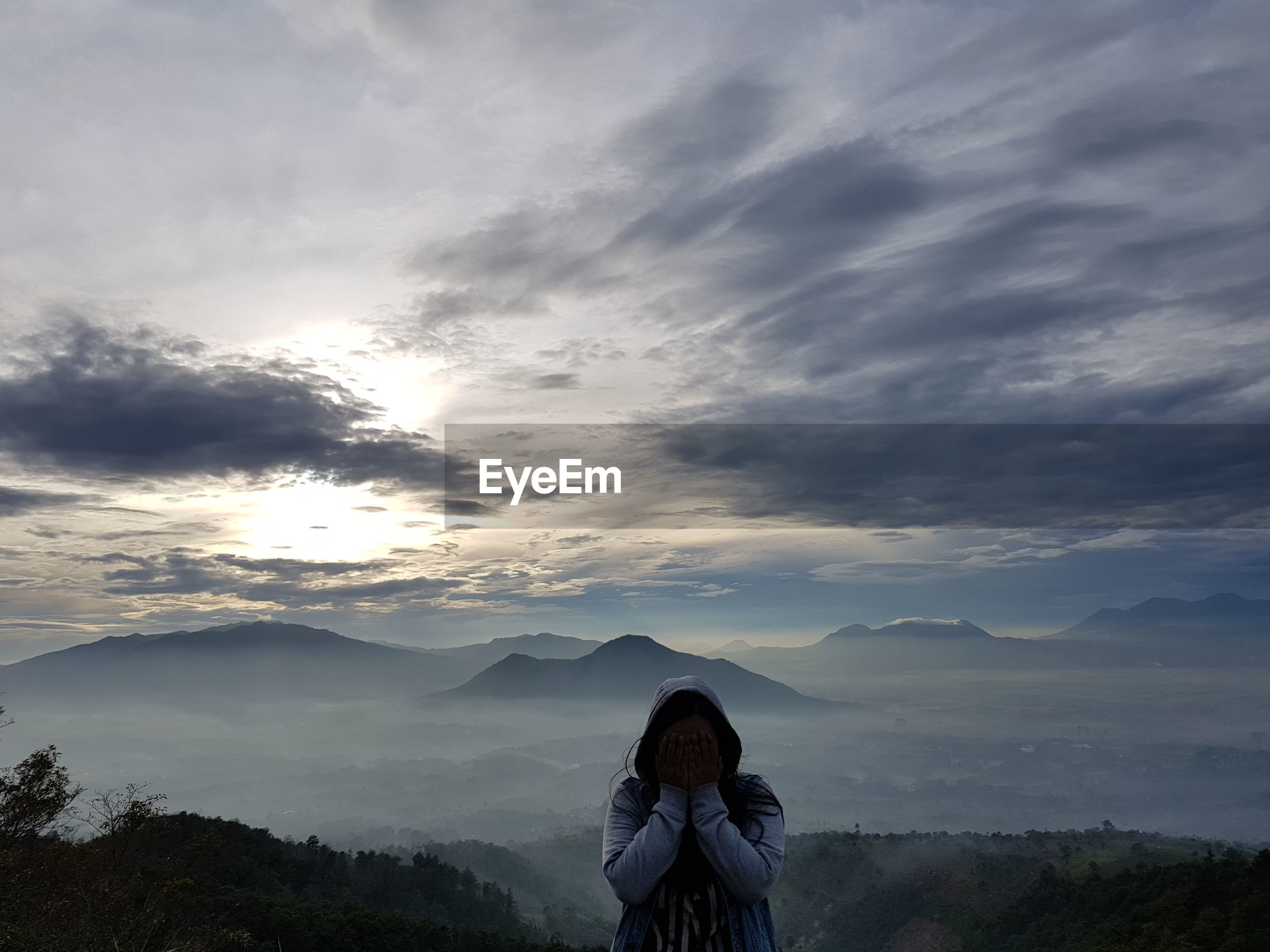 Woman covering face standing on mountains against cloudy sky