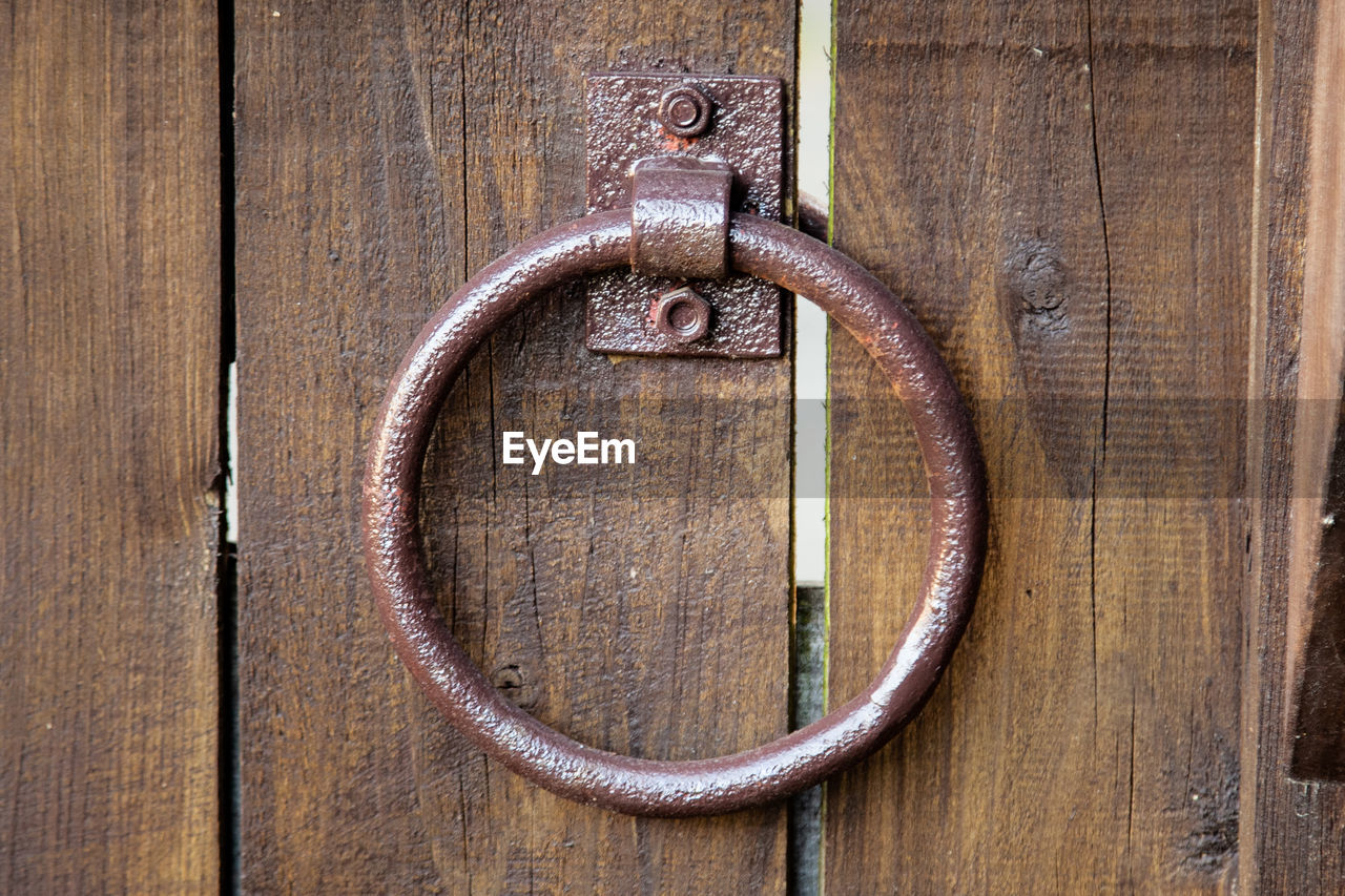wood - material, metal, close-up, no people, door, entrance, door knocker, brown, geometric shape, circle, shape, design, safety, security, old, day, handle, full frame, wood, rusty, wood grain, ornate