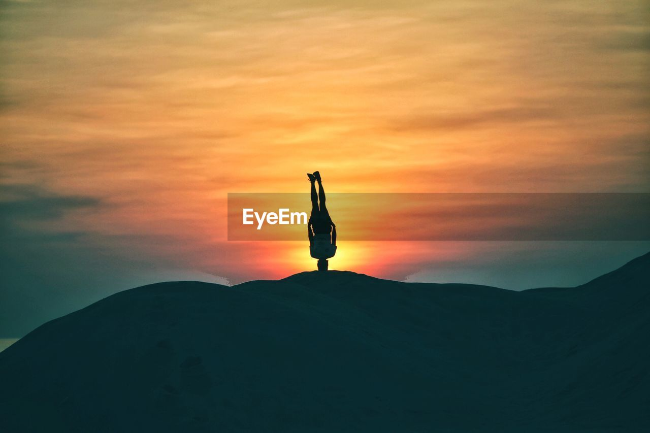 Silhouette man practicing headstand on mountain against sky during sunset