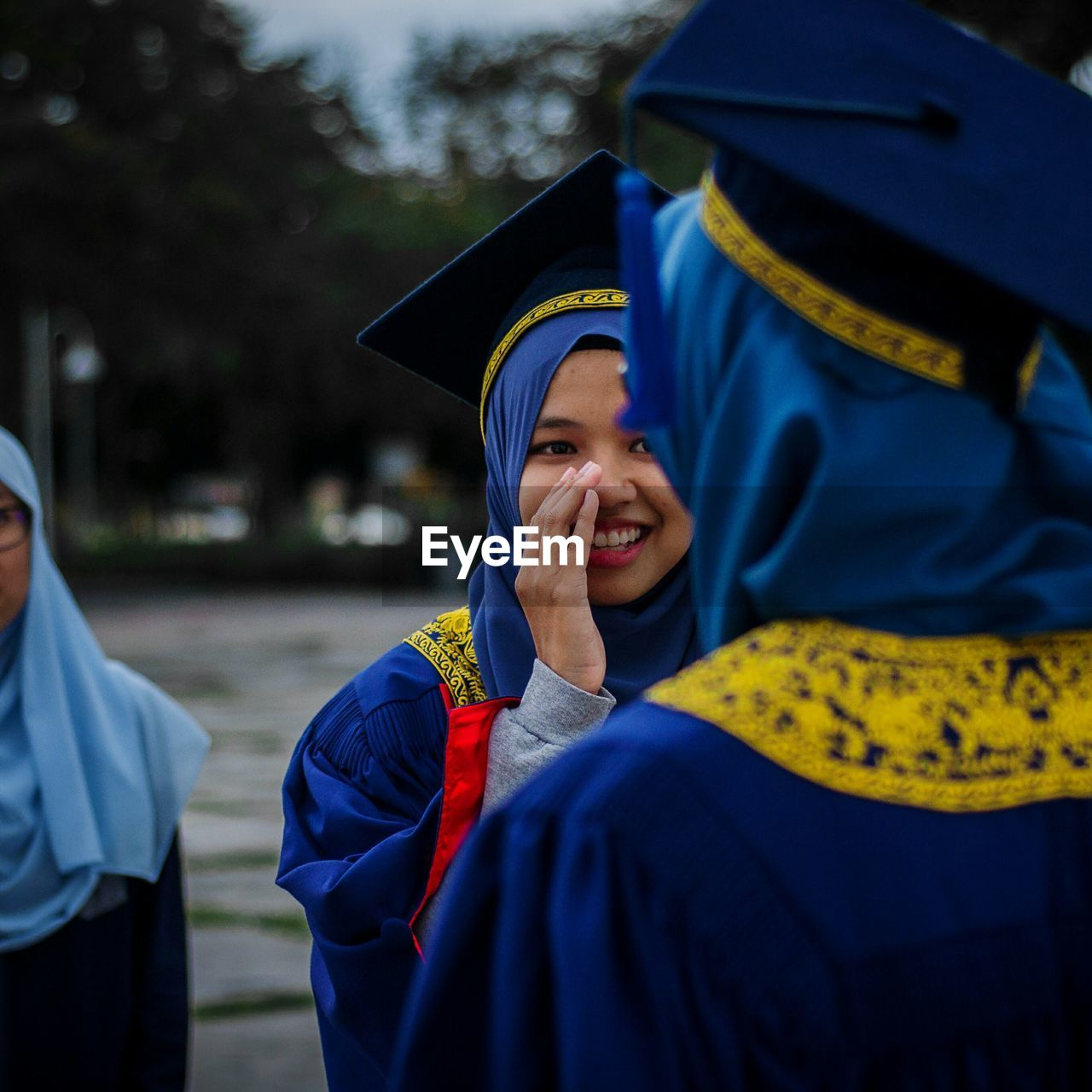 Smiling university students in graduation gowns