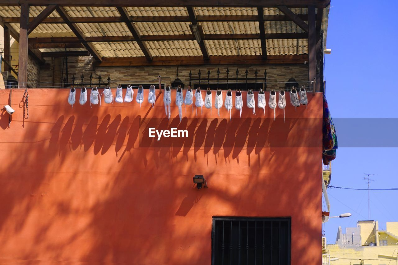 built structure, hanging, architecture, day, building exterior, no people, nature, sunlight, building, food and drink, food, drying, low angle view, orange color, outdoors, roof, brown, large group of objects, freshness, in a row