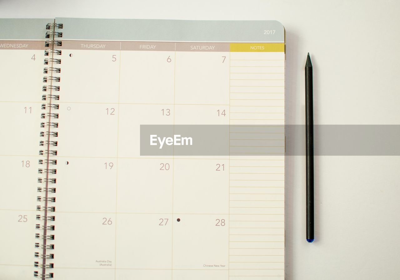 Close-up of pencil by calendar on table
