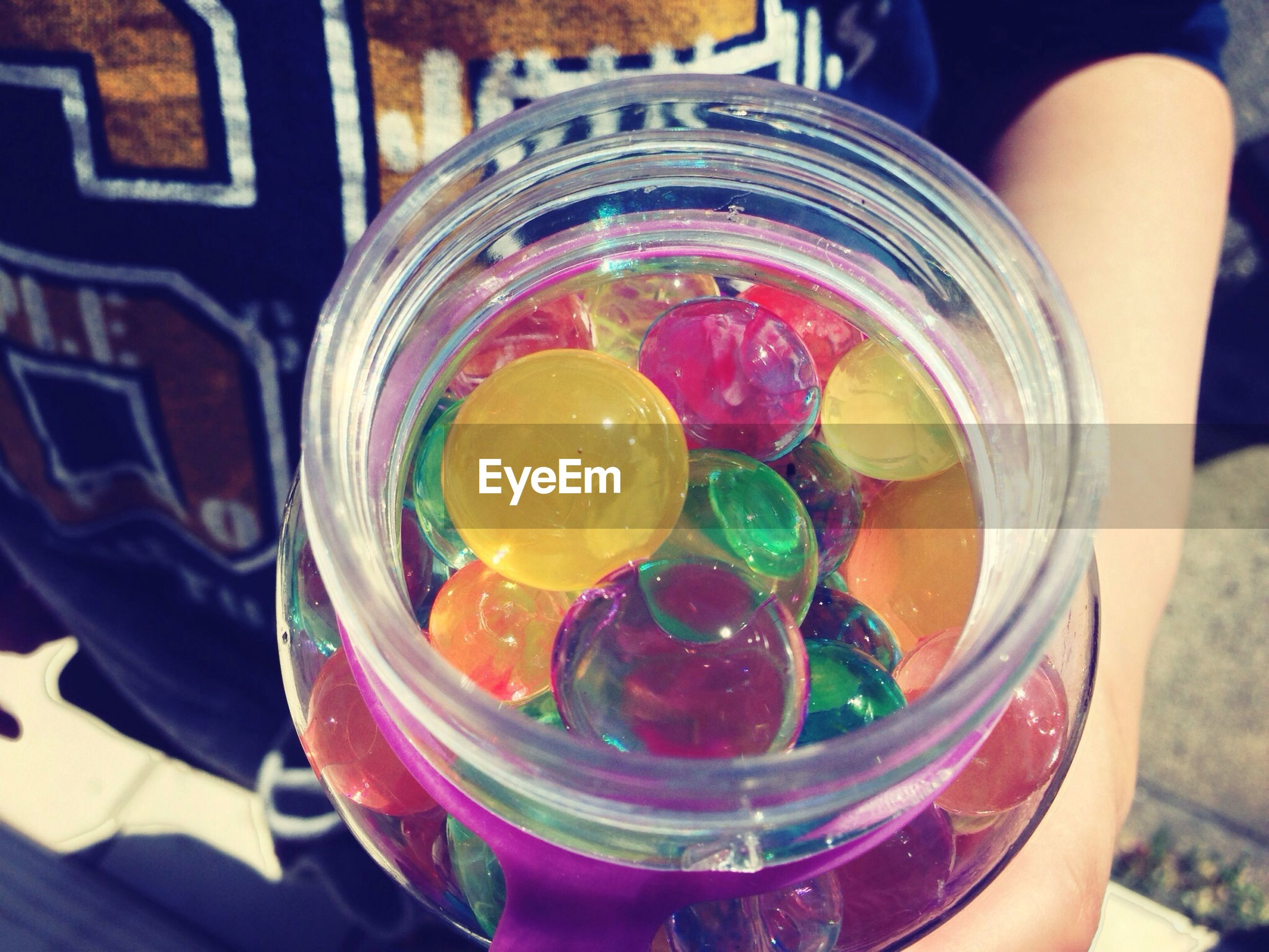 Cropped image of person holding candies in jar