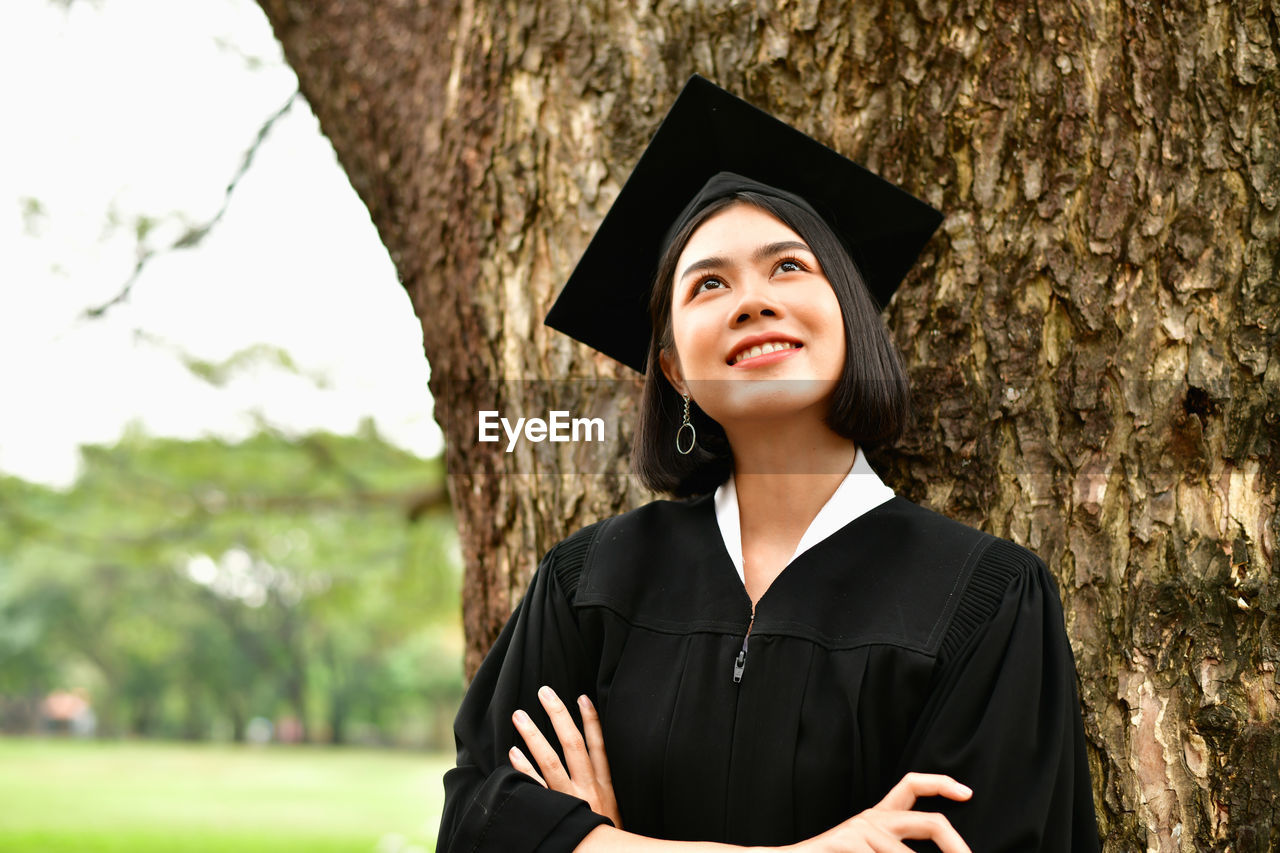 graduation gown, graduation, education, young adult, standing, mortarboard, portrait, achievement, one person, real people, young women, success, happiness, front view, student, emotion, women, nature, focus on foreground, outdoors, beautiful woman