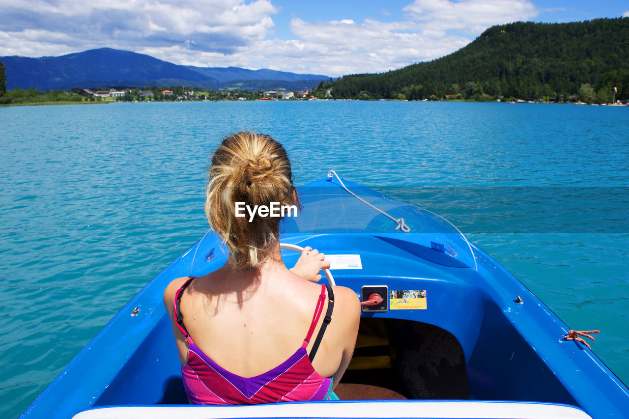 Rear view of woman steering boat in river