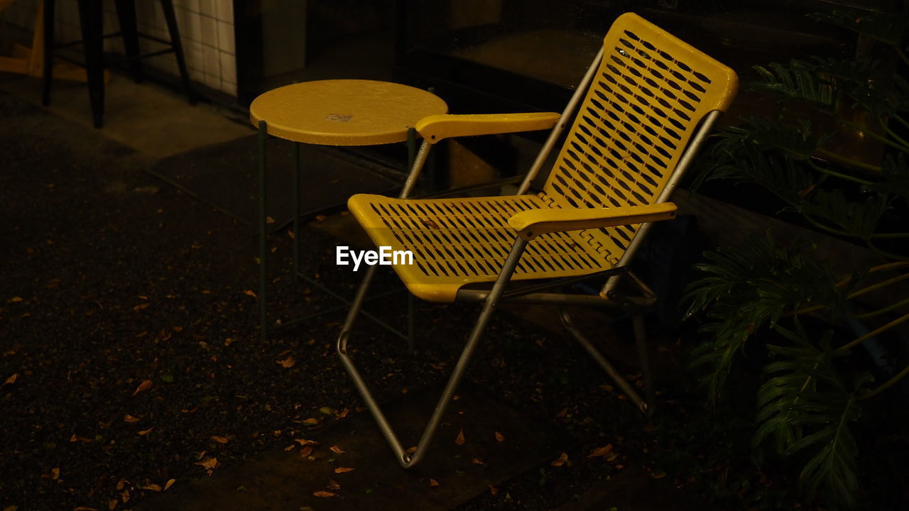 High angle view of empty chair and table in yard