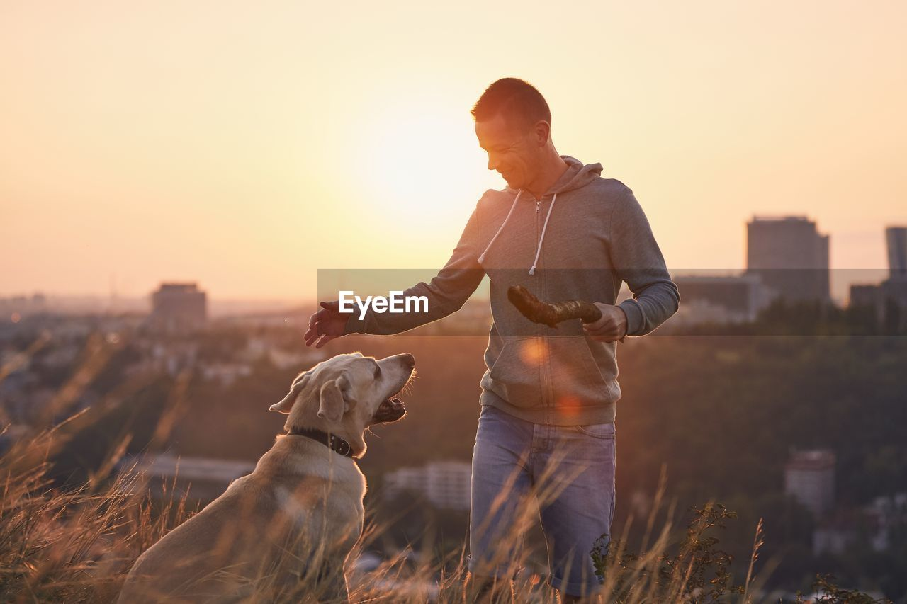 Woman with dog standing against sky during sunset