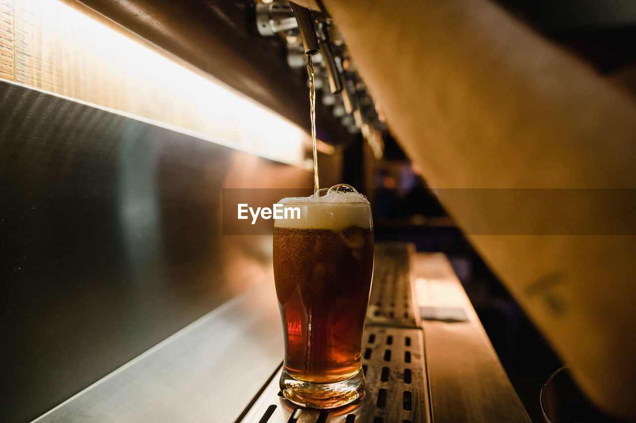 Cropped hands of man pouring beer from tap in glass