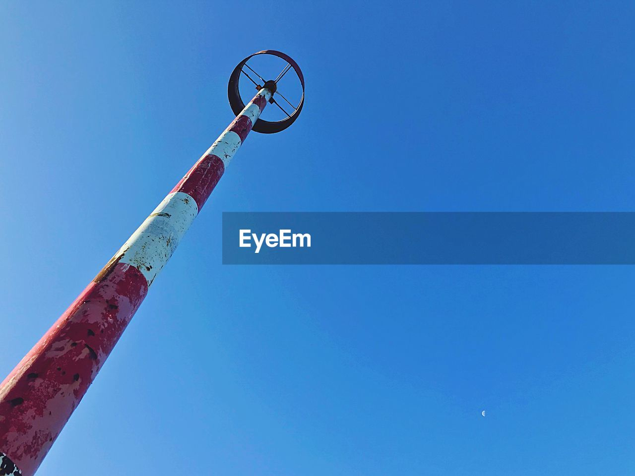 blue, clear sky, sky, low angle view, copy space, day, nature, no people, red, metal, outdoors, sunlight, pole, sport, communication, circle, geometric shape, sunny, shape, white color