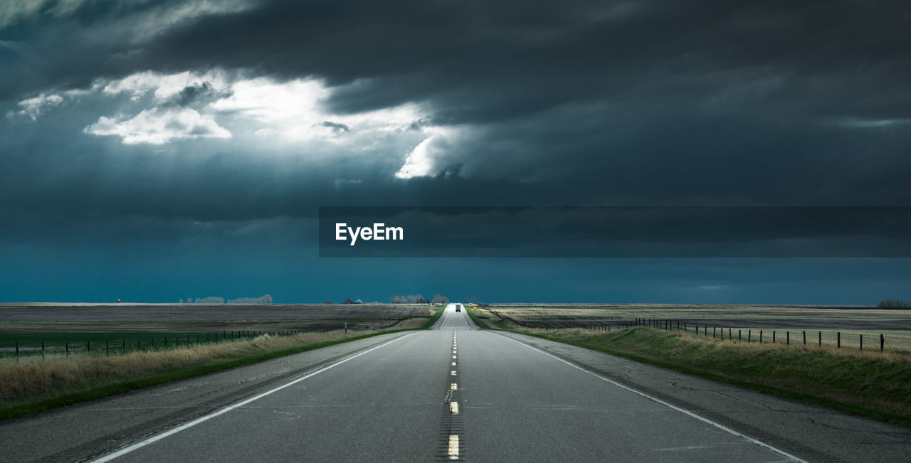 Diminishing perspective of road against cloudy sky