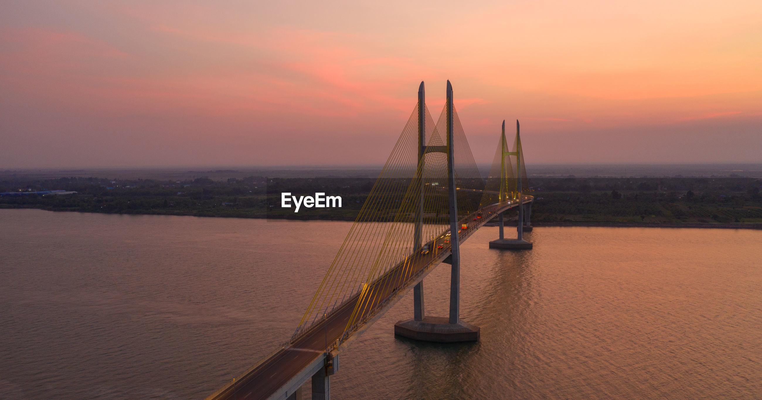 Bridge over river against romantic sky at sunrise