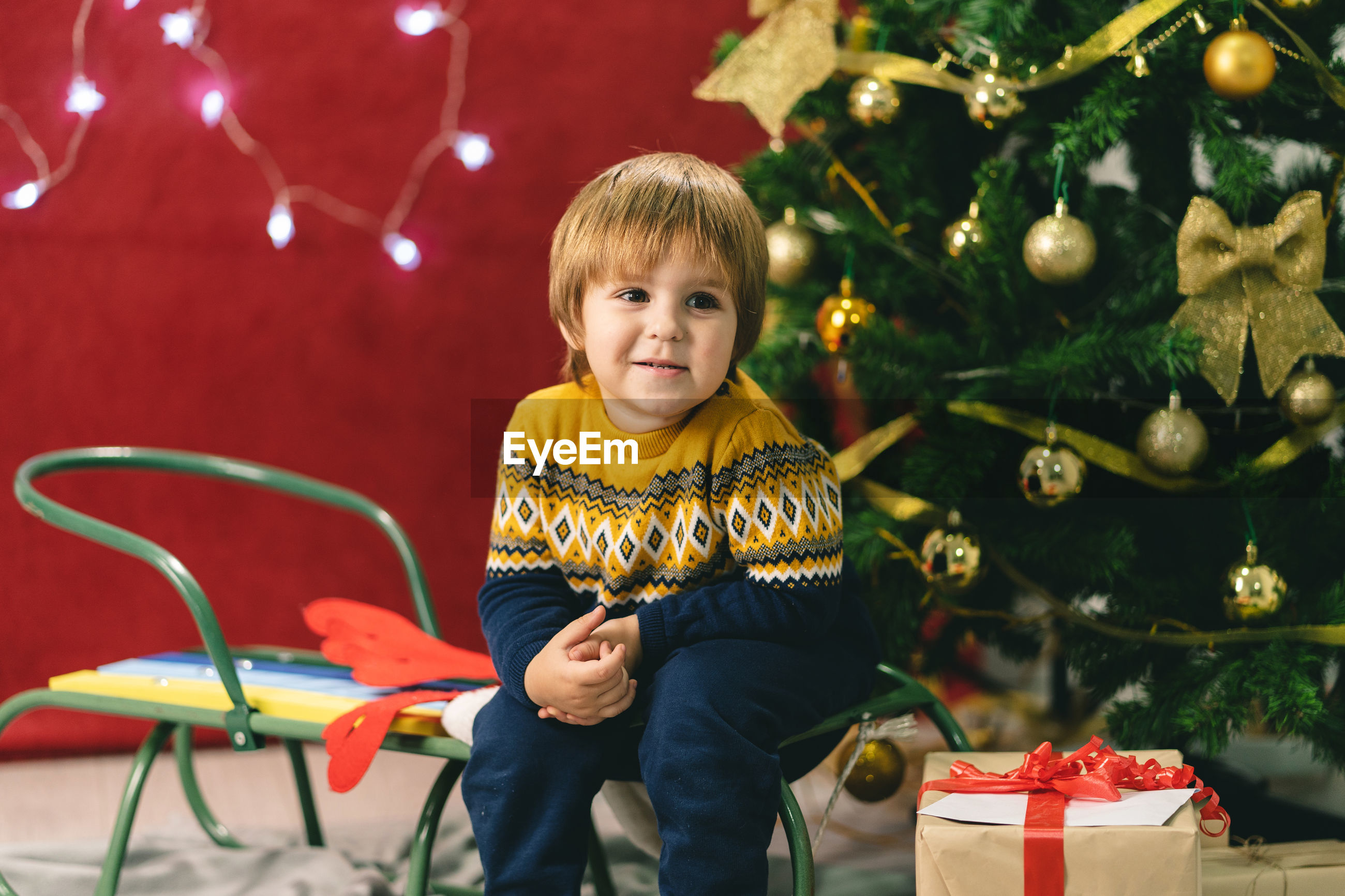 Smiling boy sitting by christmas tree