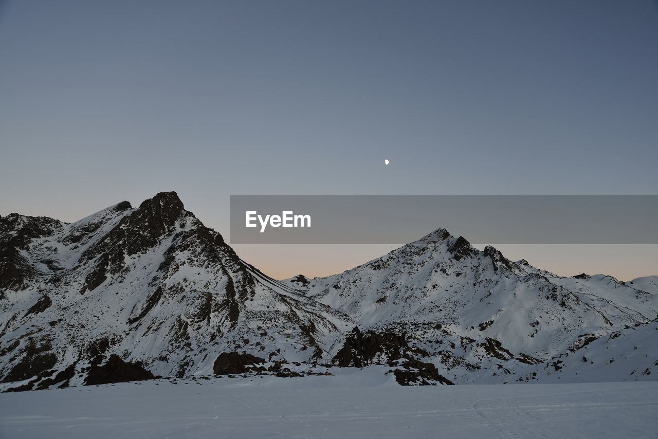 sky, snow, cold temperature, beauty in nature, mountain, scenics - nature, winter, moon, tranquil scene, tranquility, snowcapped mountain, non-urban scene, nature, idyllic, no people, mountain range, clear sky, space, environment, astronomy, full moon, mountain peak, planetary moon