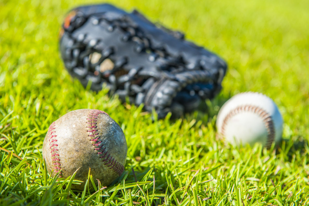 Close-up of ball with glove in background on grassy field