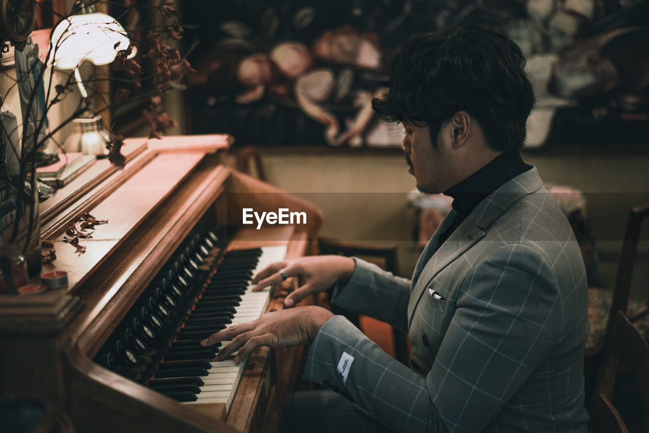 Side view of young man playing piano