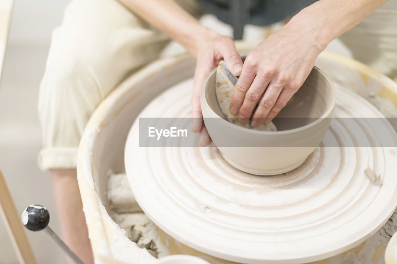 Cropped Hands Of Potter Making Container At Workshop