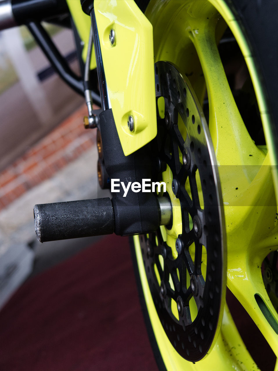 mode of transportation, land vehicle, transportation, bicycle, close-up, stationary, metal, yellow, focus on foreground, no people, handlebar, day, handle, wheel, vehicle part, pedal, high angle view, sport, motorcycle, outdoors, tire, spoke