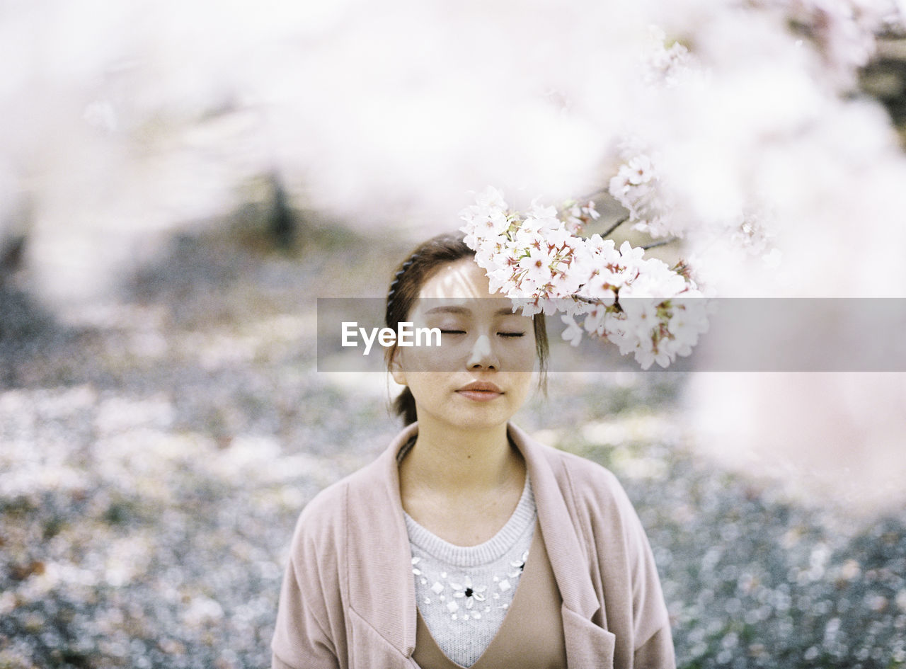 plant, flower, flowering plant, one person, nature, portrait, front view, lifestyles, real people, tree, day, young adult, leisure activity, beauty in nature, headshot, focus on foreground, growth, young women, outdoors, hairstyle, beautiful woman, contemplation, cherry blossom