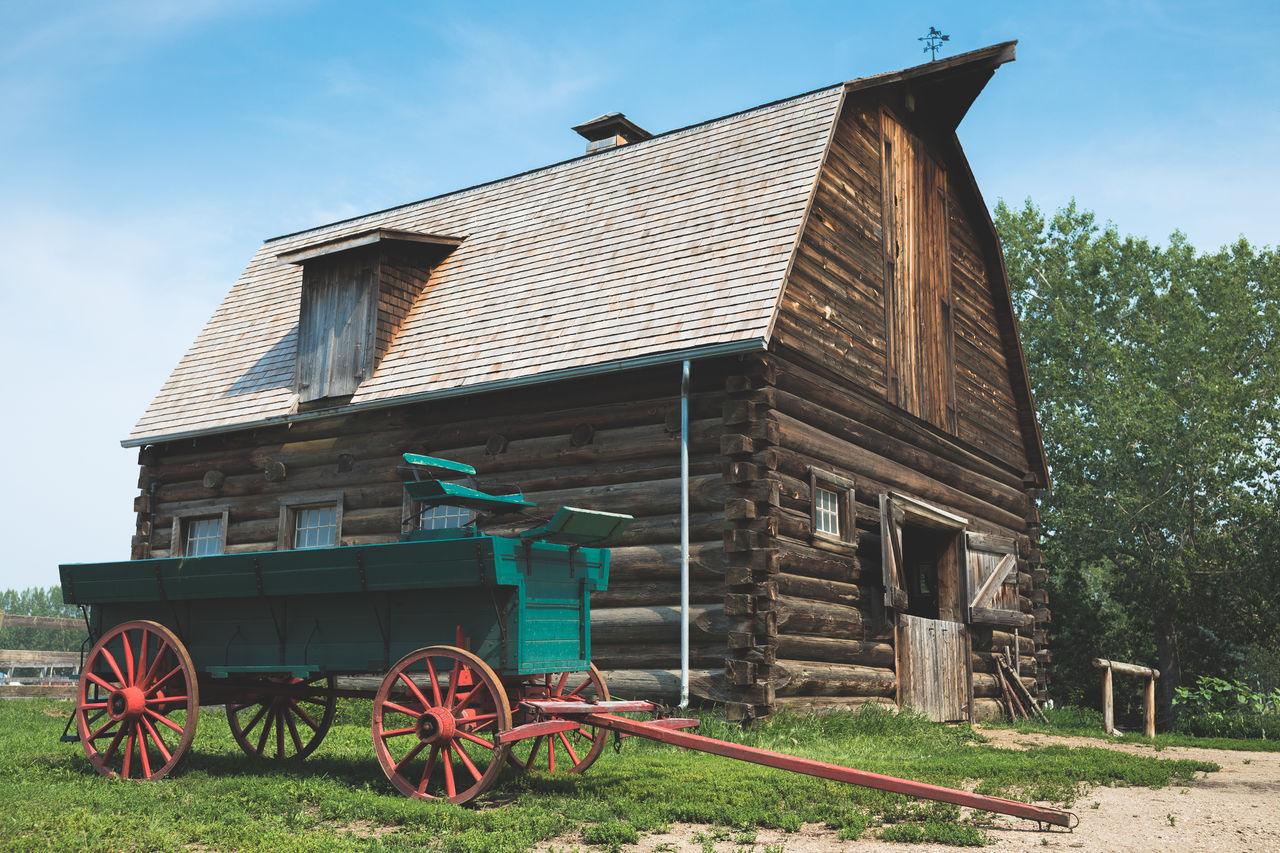 architecture, built structure, building exterior, building, sky, plant, nature, wheel, day, house, no people, grass, wood - material, cart, outdoors, field, land, transportation, history, wagon wheel