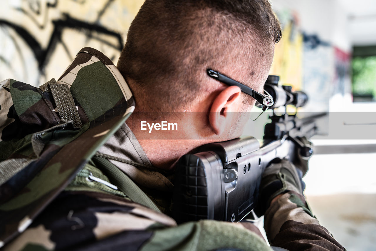 weapon, military, gun, men, headshot, real people, armed forces, one person, government, rifle, military uniform, portrait, males, uniform, army, aiming, indoors, safety, occupation, aggression
