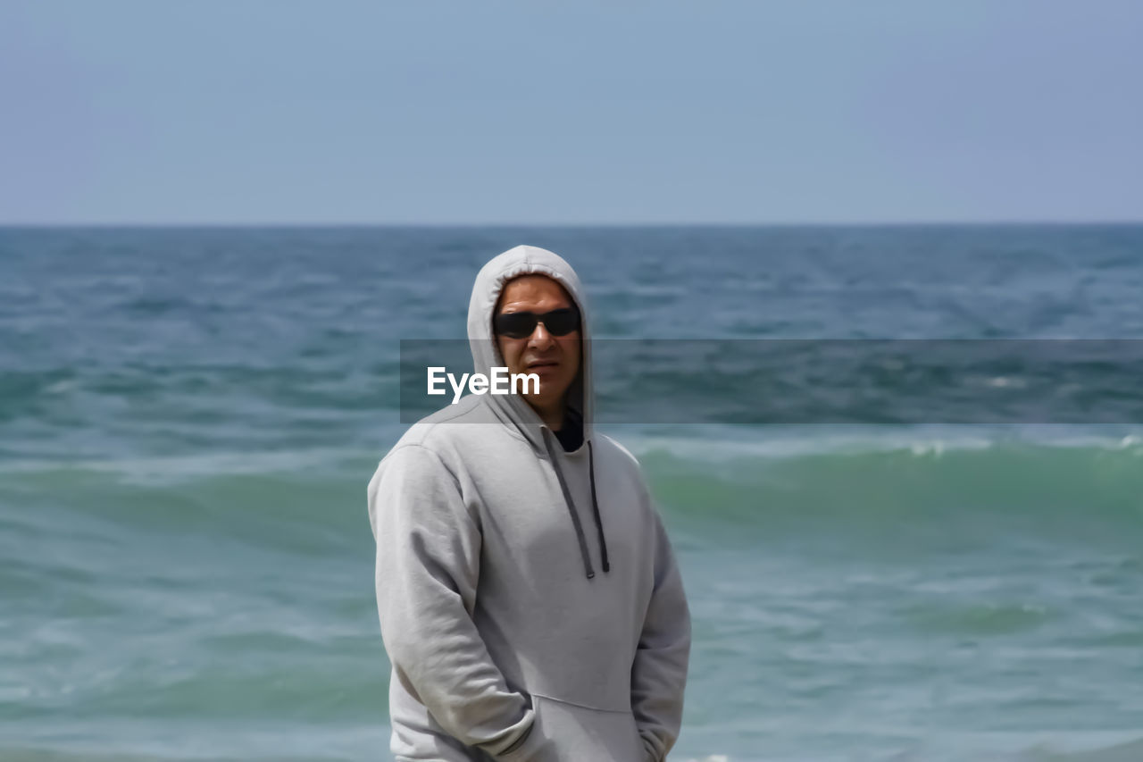 water, one person, sea, standing, portrait, looking at camera, real people, sky, beauty in nature, scenics - nature, lifestyles, glasses, leisure activity, sunglasses, horizon, day, front view, horizon over water, outdoors