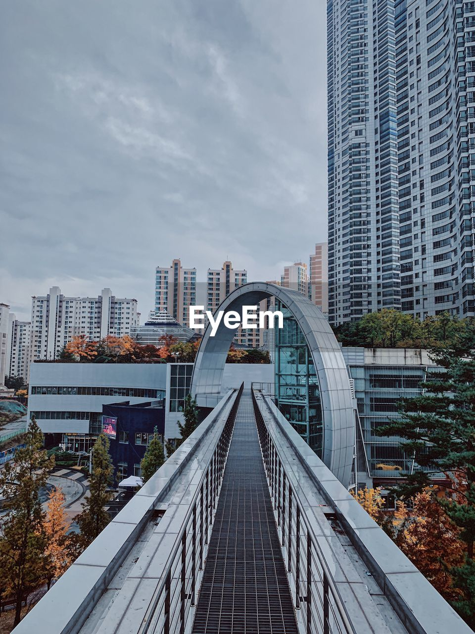 High Angle View Of Elevated Walkway Leading Towards Buildings In City Against Sky