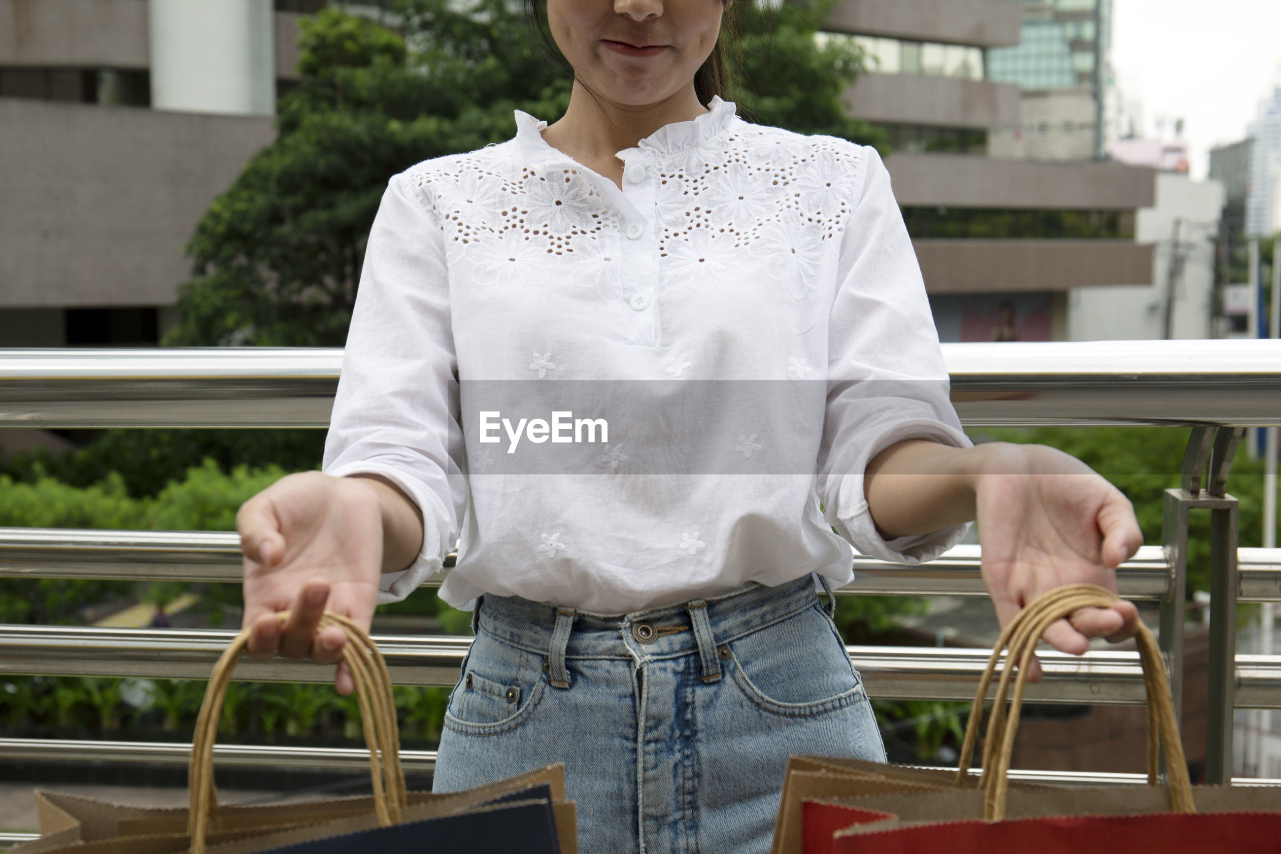 Midsection of woman holding shopping bags while standing by railing against building in city
