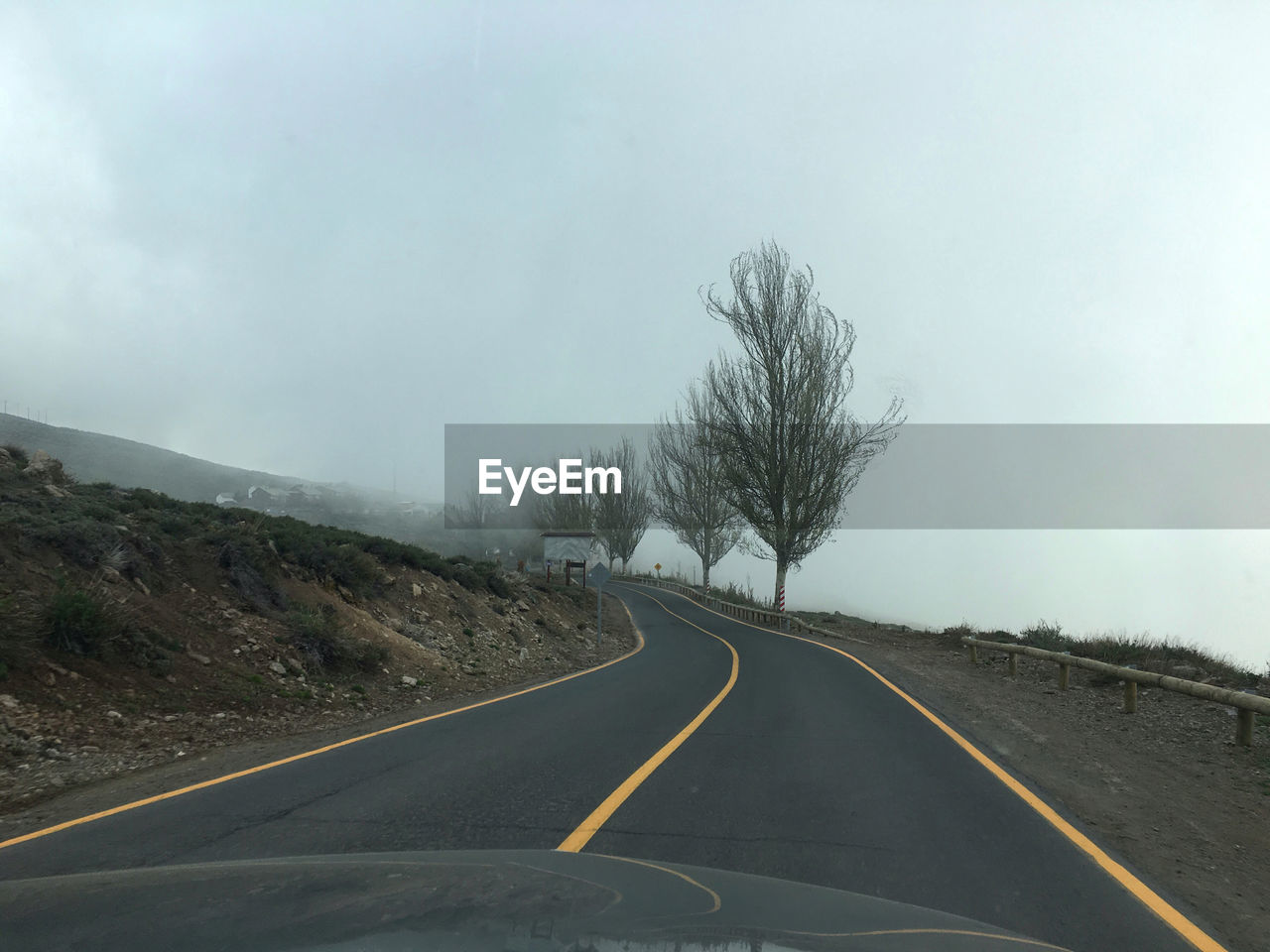 road, the way forward, transportation, landscape, road marking, nature, tranquil scene, beauty in nature, day, no people, tranquility, tree, bare tree, mountain, sky, scenics, winding road, outdoors, fog