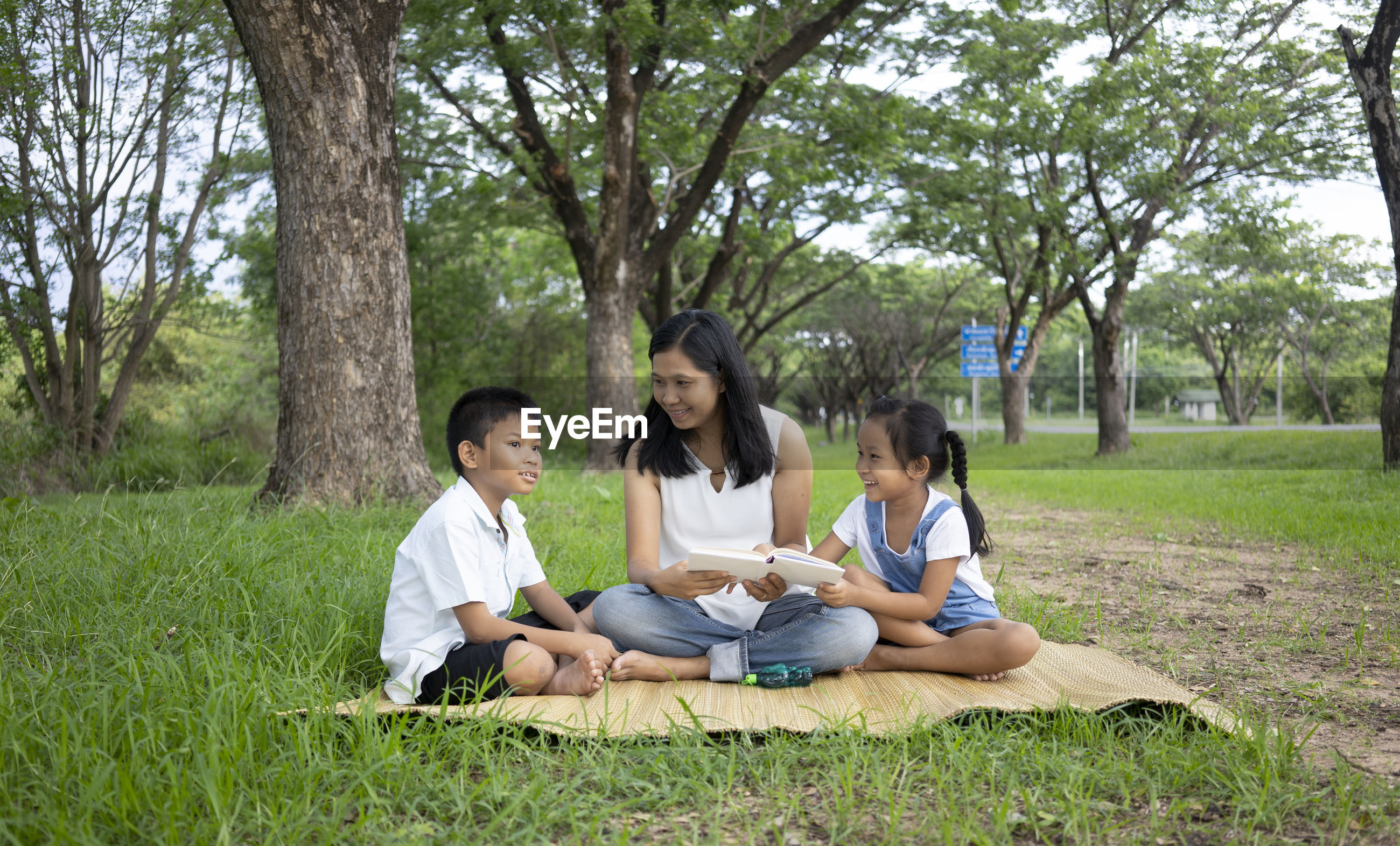Family reading book while sitting on grass against trees