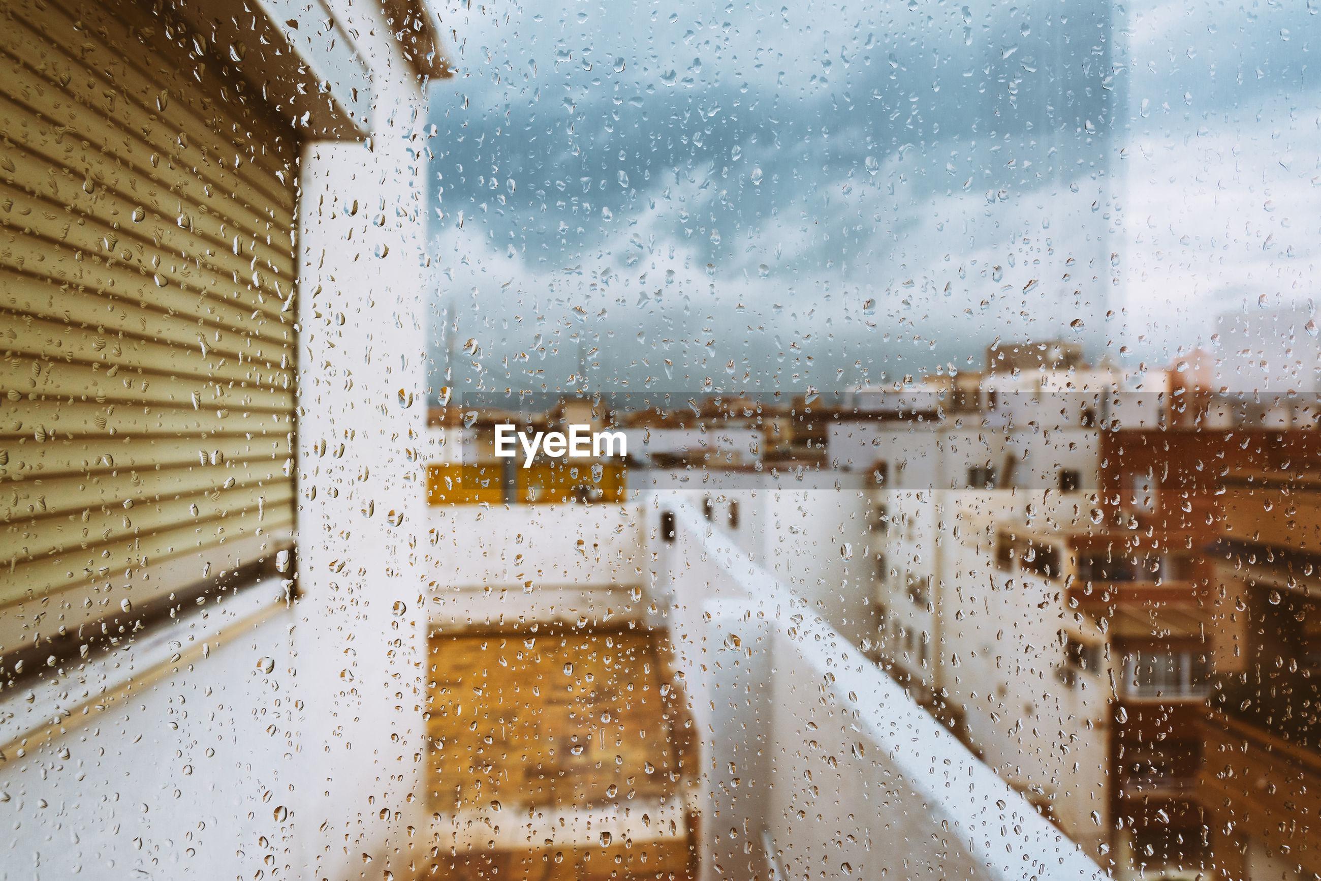 BUILDINGS SEEN THROUGH WET WINDOW