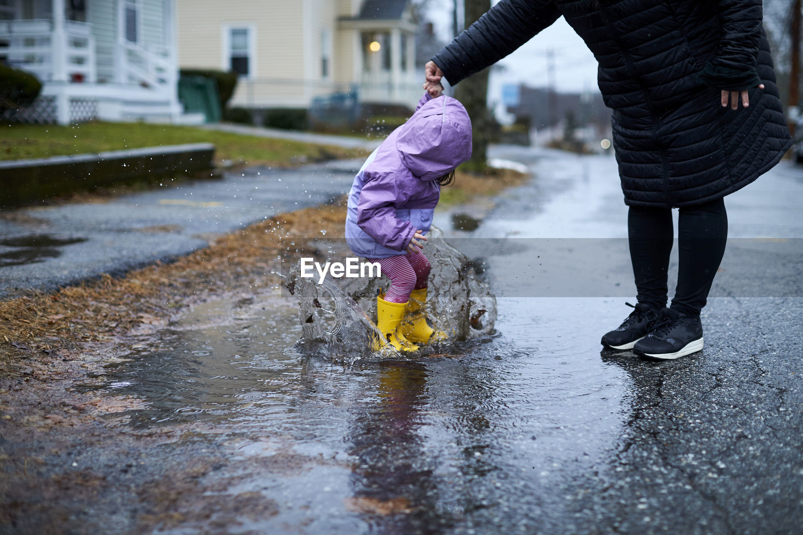 LOW SECTION OF CHILD ON PUDDLE IN RAIN