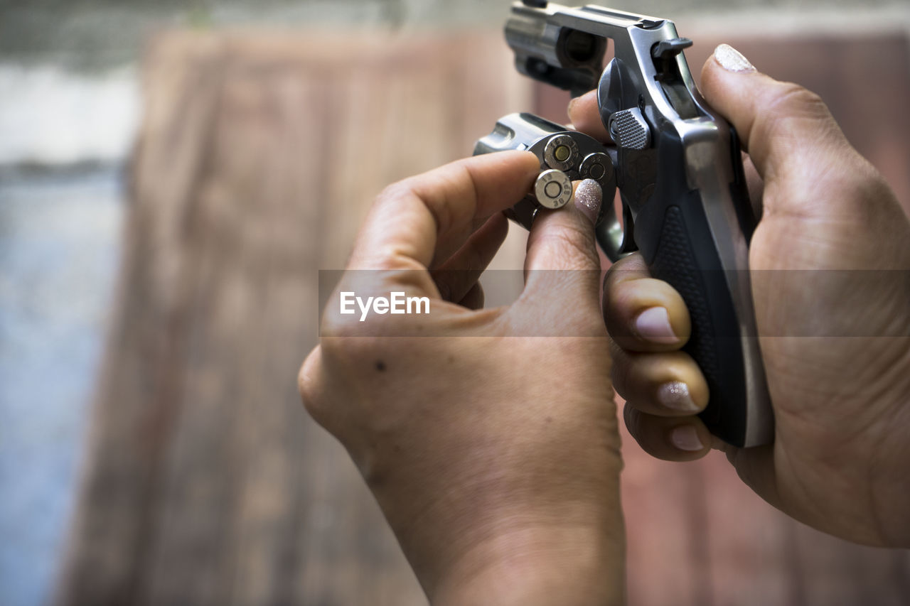 Cropped Hands Of Woman Inserting Bullets In Handgun