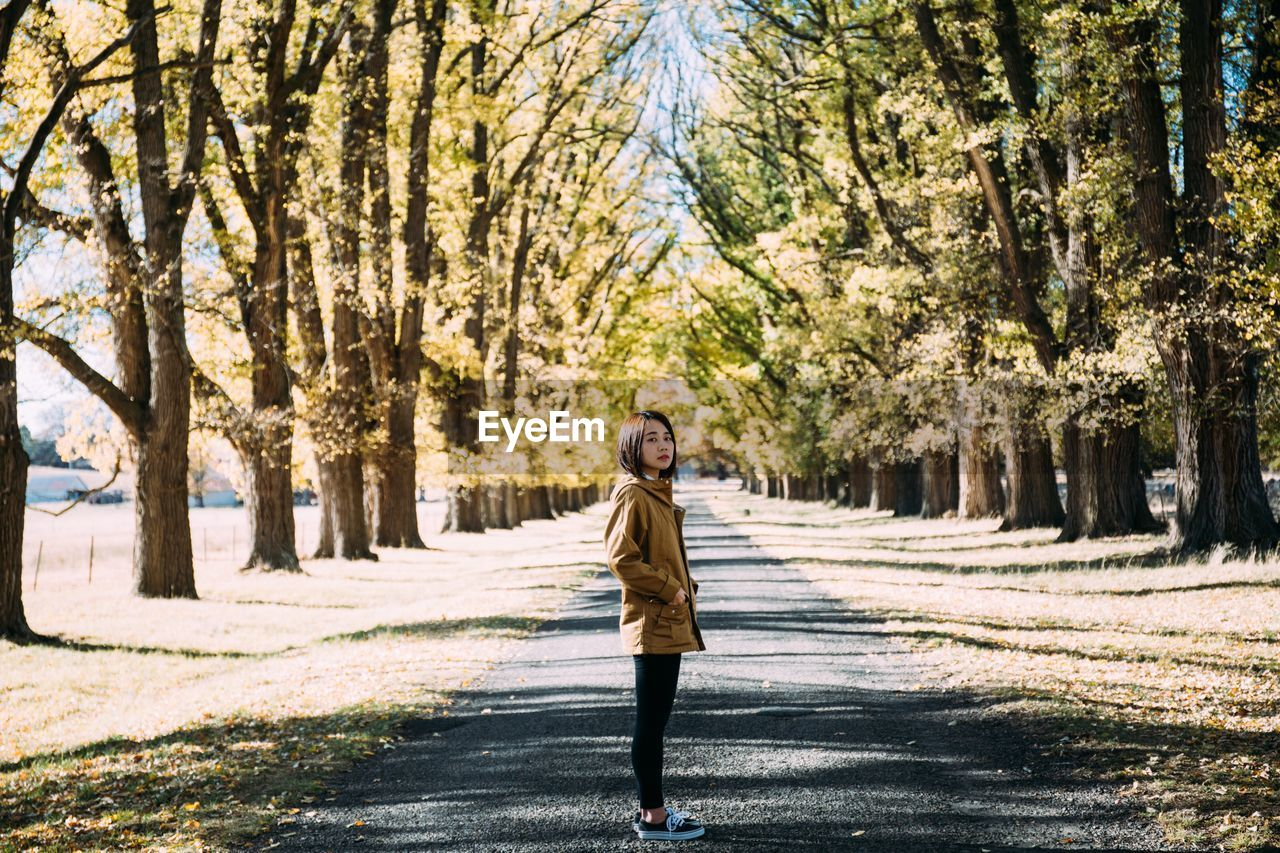 Side View Portrait Of Woman Standing On Road Amidst Trees