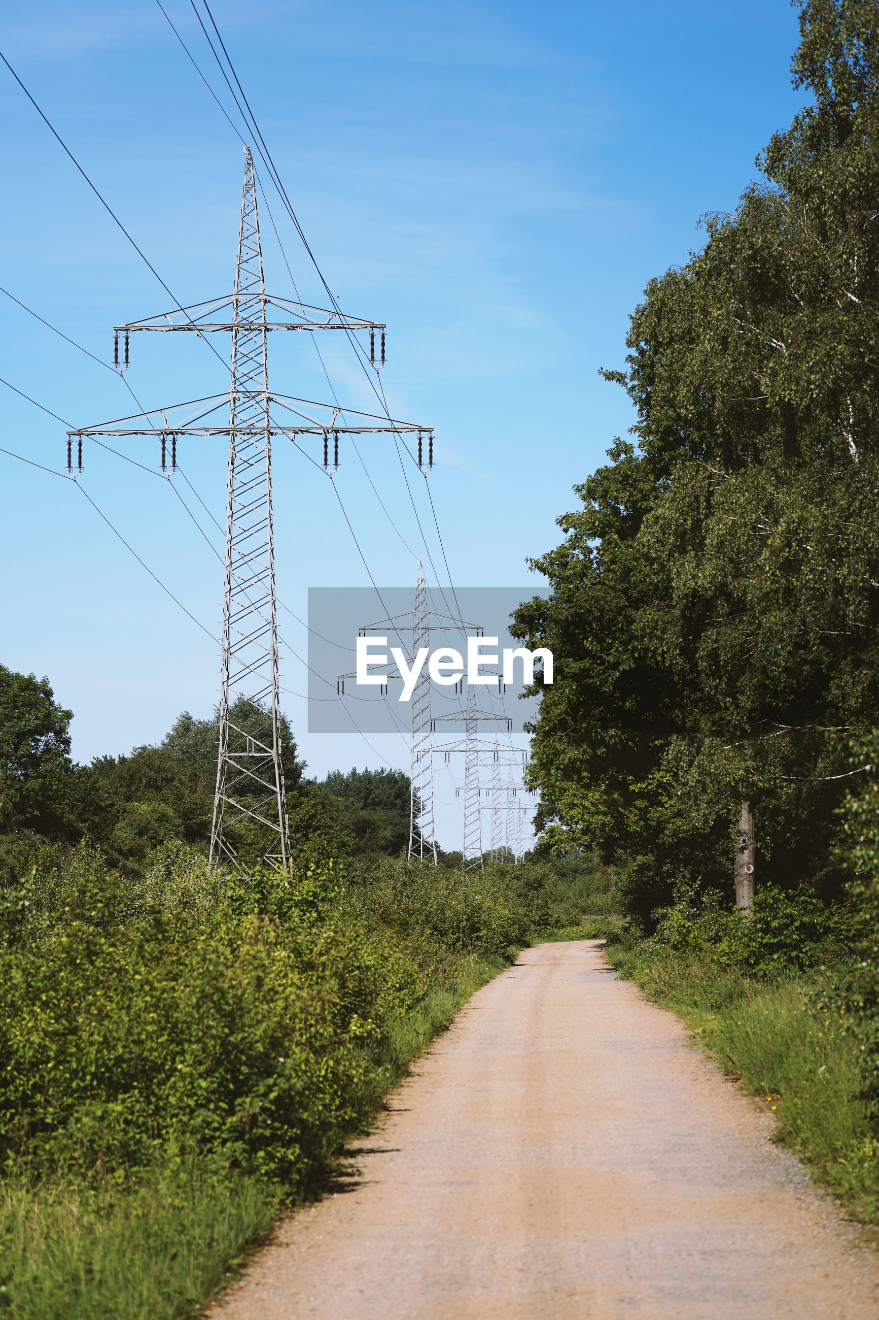Transmission line or overhead power cable with electricity pylons along rural dirt track
