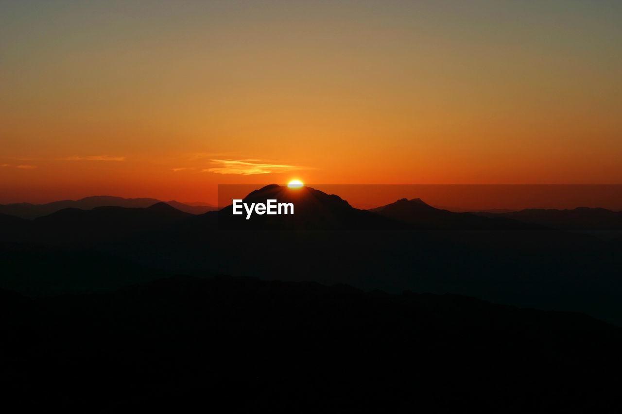 sky, sunset, mountain, beauty in nature, silhouette, tranquil scene, tranquility, scenics - nature, orange color, idyllic, mountain range, nature, copy space, environment, landscape, non-urban scene, sun, no people, remote, outdoors, mountain peak