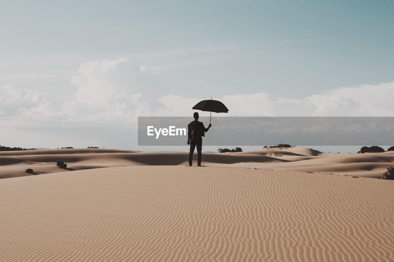 Rear View Of Man Holding Umbrella On Desert Against Sky