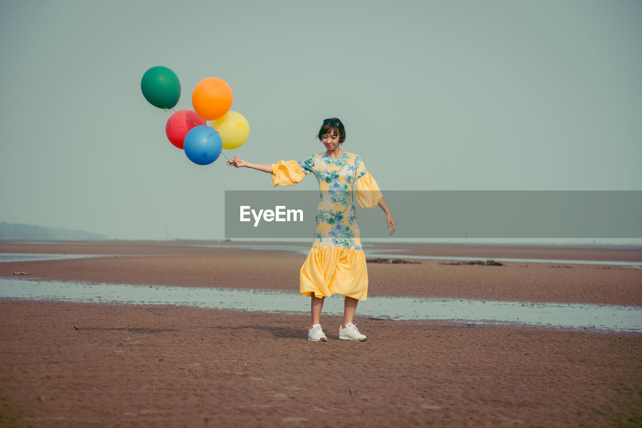 Full length of young woman holding colorful balloons at beach