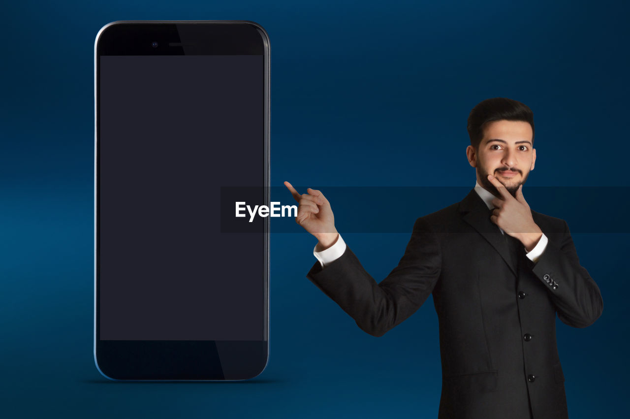 wireless technology, technology, communication, mobile phone, one person, smart phone, connection, front view, portable information device, young adult, studio shot, smiling, using phone, screen, holding, blue background, portrait, touch screen, males, telephone