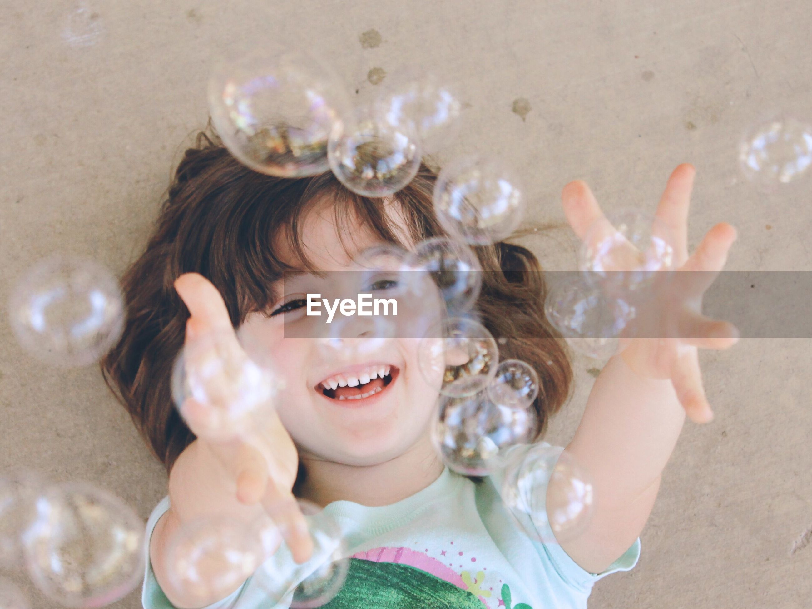 Close-up portrait of smiling girl playing with bubbles