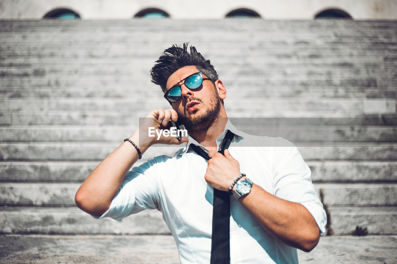 YOUNG MAN WEARING SUNGLASSES AGAINST WALL