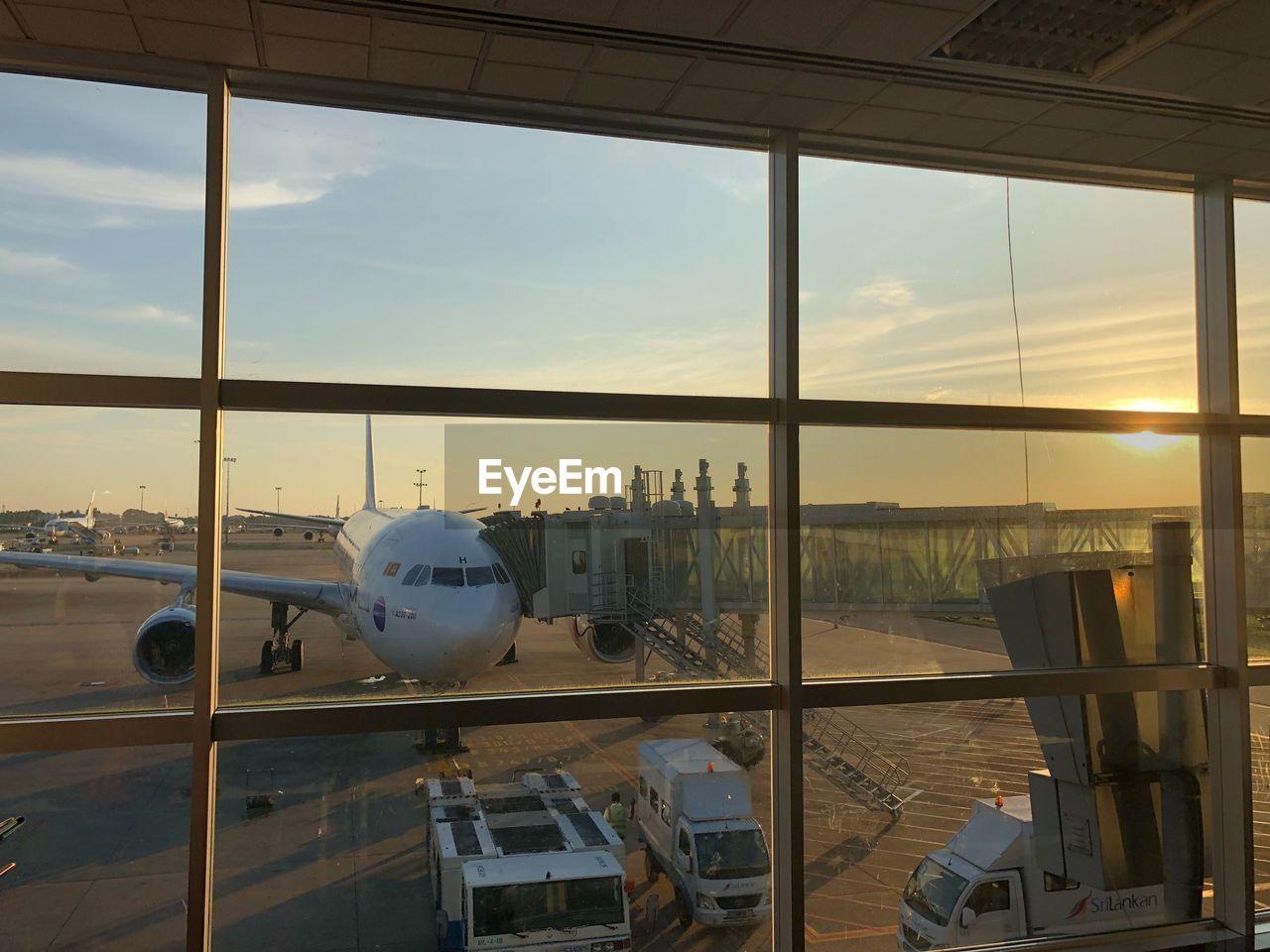 AIRPLANE SEEN THROUGH WINDOW AT SUNSET
