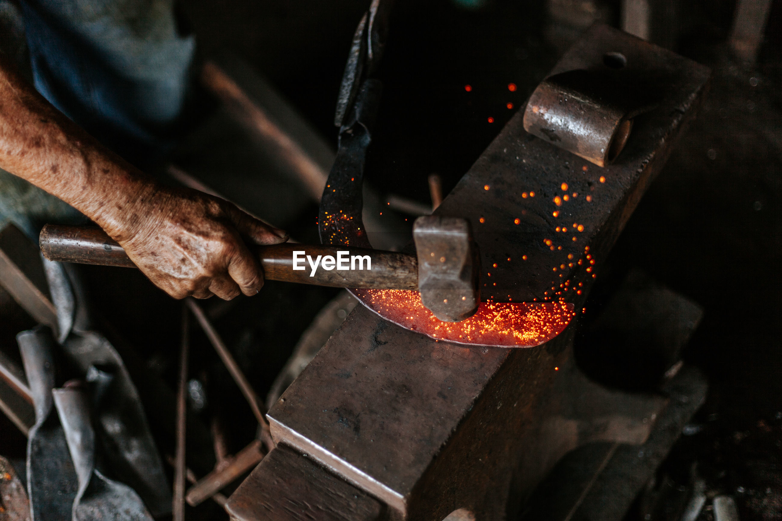 Cropped hand of manual worker hitting on molten metal in factory