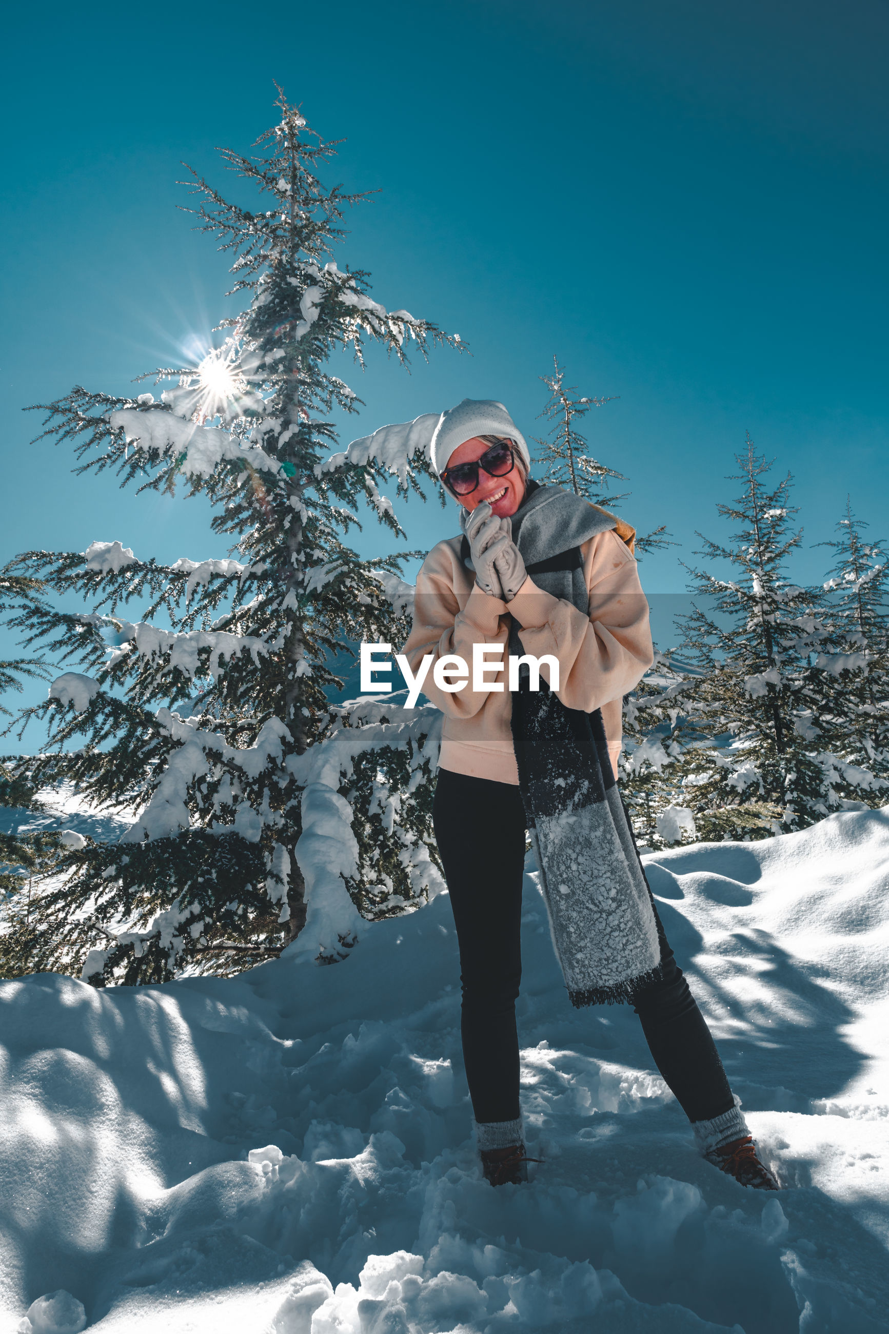 Full length of smiling woman standing on snow against tree and sky
