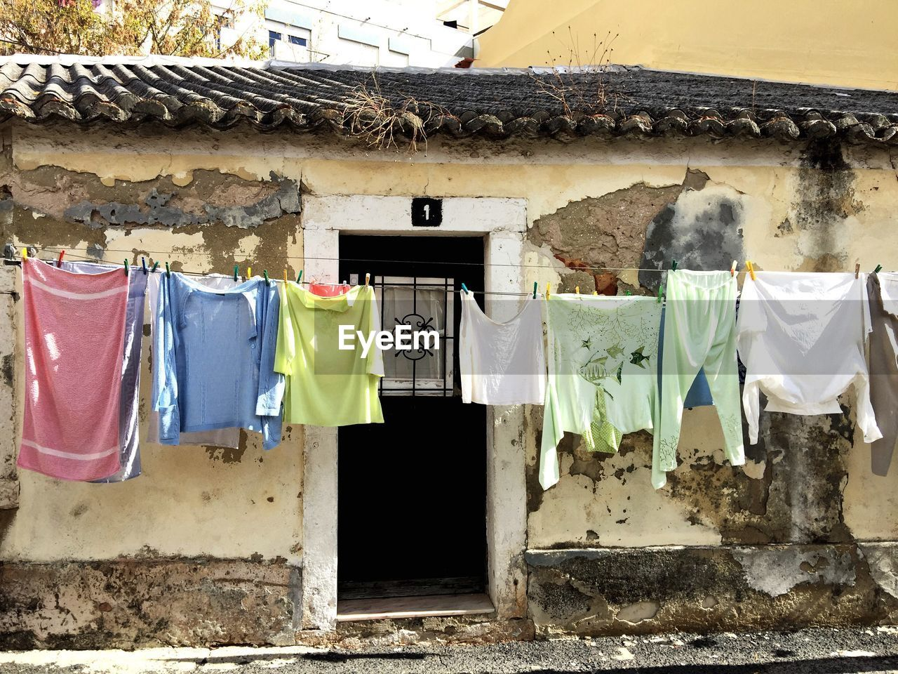 Clothes hanging against abandoned house