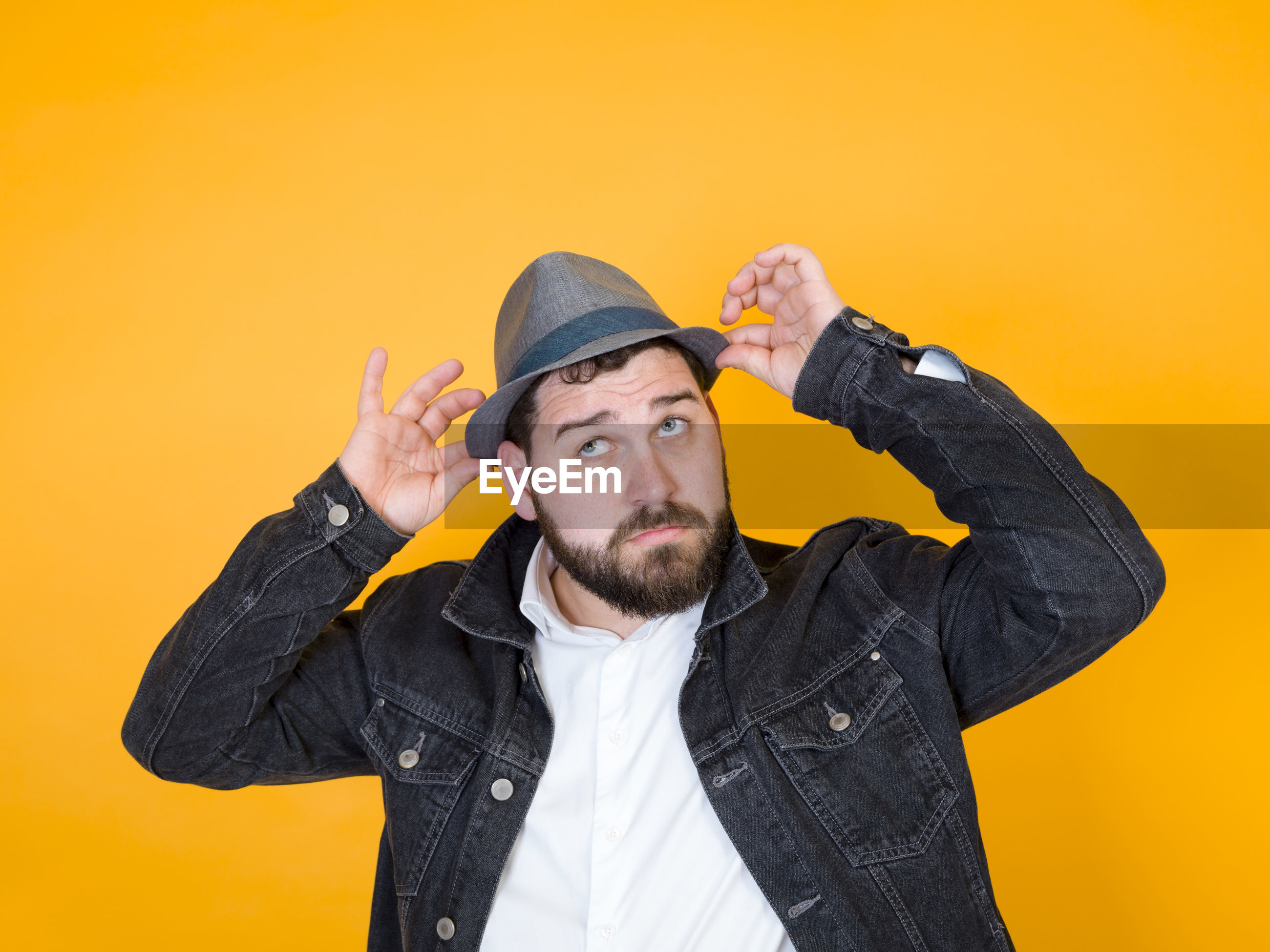 Man wearing hat while standing against orange background