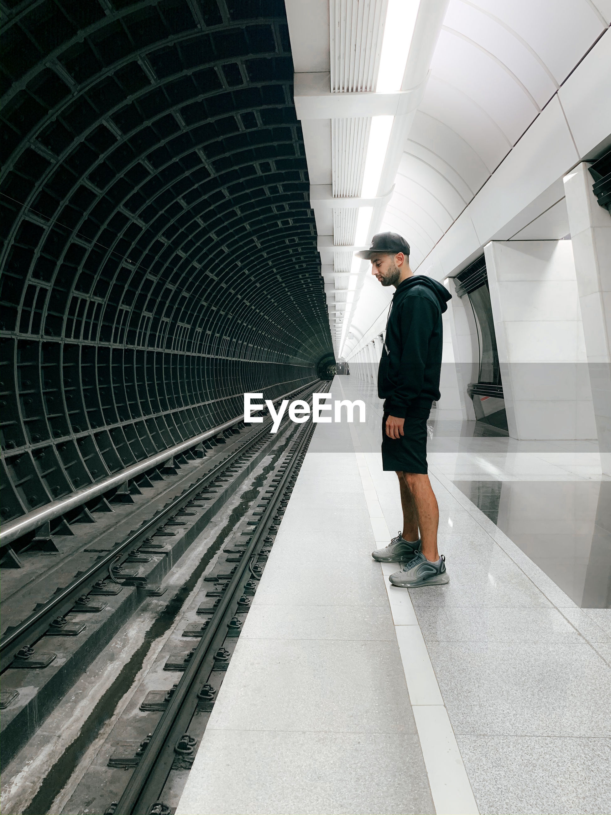 FULL LENGTH REAR VIEW OF MAN WALKING ON RAILWAY STATION